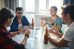 Friends playing cards stock image