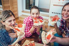Group of young friends eating pizza. Home party.Fast food concept Royalty Free Stock Photography
