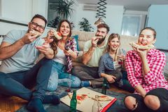 Group of young friends eating pizza. Home party.Fast food concept Stock Images