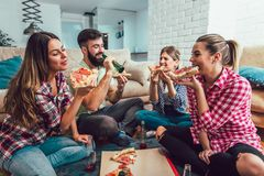Group of young friends eating pizza. Home party.Fast food concept Stock Photography