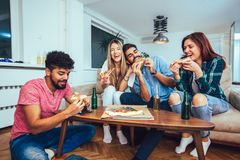 Group of young friends eating pizza. stock photo