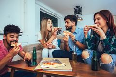 Group of young friends eating pizza. royalty free stock photography