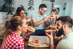 Group of young friends eating pizza. Home party.Fast food concept Stock Image