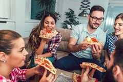 Group of young friends eating pizza. Home party.Fast food concept Royalty Free Stock Images