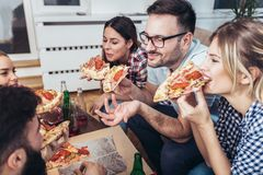 Group of young friends eating pizza. Home party.Fast food concept Royalty Free Stock Image
