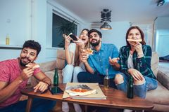 Group of young friends eating pizza and watching tv.Home party. Fast food concept Royalty Free Stock Images