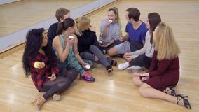 Group of young friends eats snacks one after another. Group of young people sits on the floor in light studio with food in hands. People have a break and lunch stock video