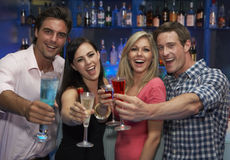 Group Of Young Friends Enjoying Drink In Bar Stock Photography