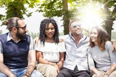 Group of young friends have fun sitting on a bench. Noutdoor in the country stock image
