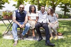 Group of young friends have fun sitting on a bench. Outdoor in the country royalty free stock photos