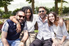 Group of young friends have fun sitting on a bench. Outdoor in the country stock image