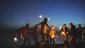 Group of young friends having a beach party. Friends dancing and celebrating with sparklers in twilight sunset stock footage