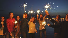 Group of young friends having a beach party. Friends dancing and celebrating with sparklers in twilight sunset stock video