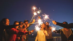 Group of young friends having a beach party. Friends dancing and celebrating with sparklers in twilight sunset. Group of young friends having a beach party stock video footage