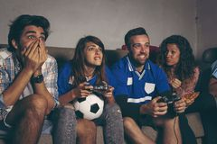 Football fans playing a football video game stock photography