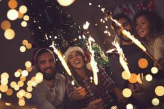 Midnight fireworks. Group of young friends having fun at a New Year`s celebration, holding sparklers at a midnight countdown Royalty Free Stock Images