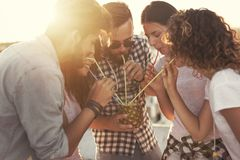 Friends drinking pineapple cocktail stock photo