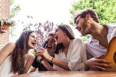 Group of young friends having fun singing a song. In the courtyard of a country house Stock Photos