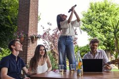 Group of young friends having fun singing a song. In the courtyard of a country house Royalty Free Stock Image