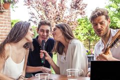 Group of young friends having fun singing a song. In the courtyard of a country house Royalty Free Stock Photo