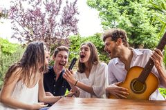 Group of young friends having fun singing a song. In the courtyard of a country house Stock Images