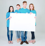 Group of young friends holding a blank board, isolated on white background Royalty Free Stock Images