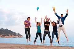 Group of young friends jumping on beach. Stock Image
