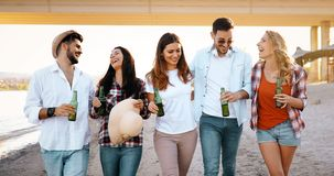 Group of young friends laughing and drinking beer. At beach stock images