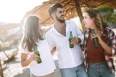 Group of young friends laughing and drinking beer. At beach royalty free stock photography