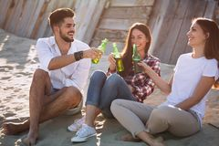Group of young friends laughing and drinking beer. At beach Stock Photography