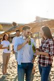 Group of young friends laughing and drinking beer. At beach royalty free stock photo