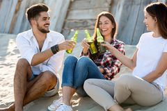 Group of young friends laughing and drinking beer. At beach stock photos