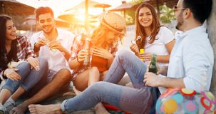 Group of young friends laughing and drinking beer. At beach royalty free stock image