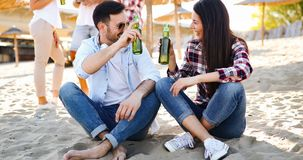 Group of young friends laughing and drinking beer. At beach stock photo