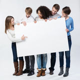 Group of young friends looking at a blank sign. Group of young friends in trendy winter fashion stock images