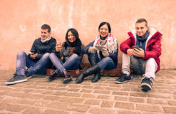 Group of young friends looking their smartphones in old town. Center - Happy people having fun together - Technology and social network concept - Warm brown Royalty Free Stock Photos
