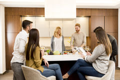 Group of young friends in modern kitchen. Group of young friends are in modern kitchen, talking to each other while preparing food royalty free stock photos