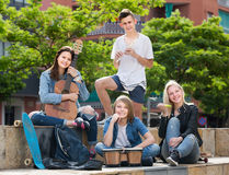 Group of young friends musicians in park. Group of young friends musicians with instruments in park on summer day Royalty Free Stock Photo