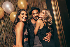 Group of young friends in a party at nightclub. Portrait of handsome men with female friends at disco. Young friends in a party at nightclub Royalty Free Stock Images