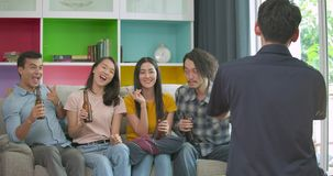 Group of young friends partying and enjoying to taking photo on couch together at home.