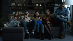 Group of young friends phubbing each other at home stock video footage