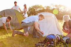 Group Of Young Friends Pitching Tents On Camping Holiday Stock Image