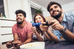 Group of young friends play video games together. At home Stock Images