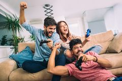 Group of young friends play video games together. At home Royalty Free Stock Image