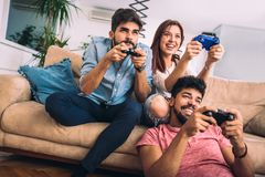 Group of young friends play video games together. At home Stock Photography