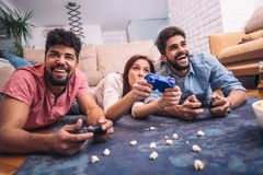 Group of young friends play video games together. At home Stock Photo