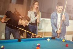 Group of young friends playing billiard Stock Photography