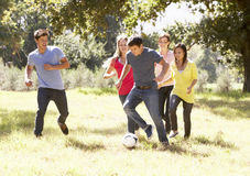 Group Of Young Friends Playing Soccer In Countryside stock photos