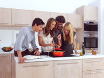 Group Of Young Friends. Preparing Breakfast In Modern Kitchen stock image
