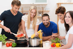 Group of young friends preparing pasta. Group of diverse young friends preparing pasta standing around the stove cooking spaghetti and a tomato based sauce Royalty Free Stock Photography